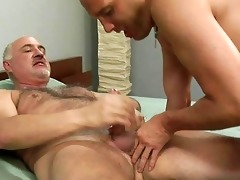 older gay gives younger hunk a tugjob on couch